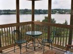 A view from within the screened porch looking over the water. There is also a comfortable glider