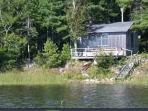 View from the lake of the additional cabin-easy chairs and woodstove and a deck at the water's edge.
