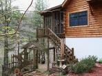 Back porch with steps leading to hot tub on river bluff