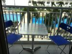 balcony with table+chairs, view on the pools