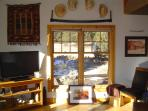 Portion of the living room showing 2 of 5 sumptuously large windows in this sunlight filled room.