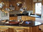 Kitchen with island stove, refrigerator (2nd in the bar and a 3rd in the garage) double oven, microwave