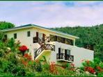Moondance is a charming villa located on a hillside overlooking the sea.