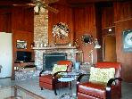 Bright living room: Large brick fireplace, wall-mount TV/soundbar, and leather chairs