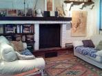The living room has a log fireplace, two comfortable sofas and plenty of books and guides