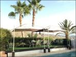 LARGE AREA OF TABLES, DINING, DINNER WITH SHADOW IN THE POOL AND BARBECUE
