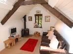 Mill Barn's living room is warm and cosy with seating for two in front of the wood burner and S