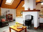 Horseshoe Cottage living has a high beamed ceiling and a feature chimney with wood burning stove