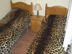 Twin room downstairs leading from living area with wardrobes,safe and bathroom