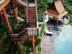 Wooden stairs down to tropical garden and swimming pool