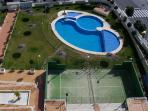 large spacious pool with enclosed shallow part for youngsters and babies and a tennis court