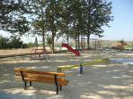 Children's play area, shaded by trees, with tennis court behind - 2 minutes from the villa