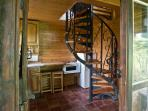 Spiral staircase in the kitchen is lit by fairy lights at night.