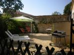 Private courtyard garden with loungers, table & chairs & a barbecue