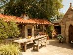 The Barbecue has a Mediterranean feel, with a wonderful table to seat many, next to Ruth's Cottage.