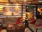 Elegant yet comfortable sofas; unique wall art displayed on the log & chink cabin walls