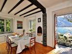 The lake view dining room with parquet flooring features a charming working stone fire place