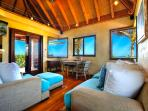 Living room with high ceilings with large windows on each side with views of the beaches