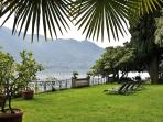 The pretty garden features a picturesque lawn, a sunny lakefront terrace with modernist sun loungers