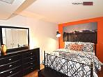 Chic master bedroom with queen size bed, dresser and walk in closet