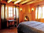 Romantic bedroom showing wood burning kiva fireplace for ambiance and chilly mountain evenings