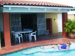 Relax in the shade under the covered lanai, while other swim in the pool.
