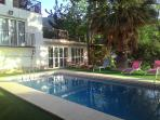Pool with games room in background surrounded by wonderful trees creating a paradise