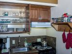 Cupboards are stocked with dishes and glasses.  Spices, coffees, cooking oil and utensils.
