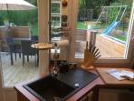 Clear view of the rear terrace and garden from the kitchen, kids safely in view at all times