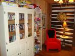 Awesome Massage Chair in corner of Living Room with Cabinet of DVD, Books & Games, Stuffed Animals