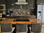 High End Kitchen with marble counter tops , breakfast bar and stainless steel appliances
