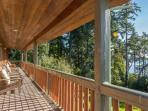 Southwest covered deck with comfy adirondack chairs and tables.  Bay and woodland views.