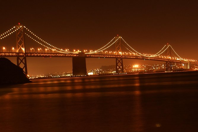 Experience San Francisco at Night in a Luxury SUV with a glass of champagne