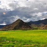 蓝天、白云、黄褐的山,黄色的油菜地,一幅人间美景