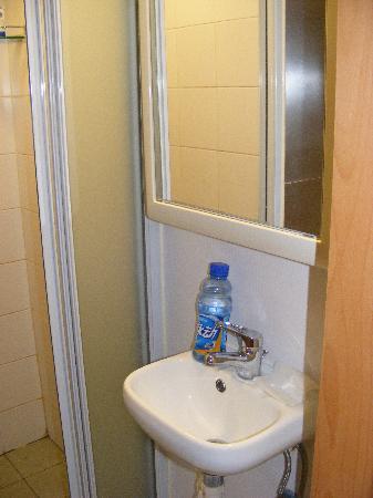 迷你的洗脸池,特意放了瓶饮料做比较,旁边就是可以拉上的门,里面是洗澡的,只能站着,半蹲都很勉强