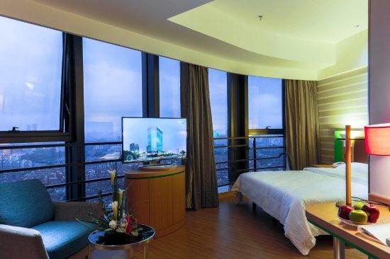 Nantong, China: 酒店的主推房型,38平米豪华大床房,位于酒店20-25层,全景落地玻璃,转角沙发