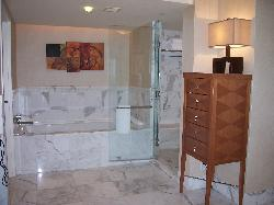 marble bath and shower with bench