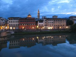 Early evening view of the Arno and the illuminated city across