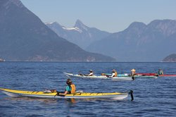 Mt Denman in the background as kayakers cross Desolation Sound