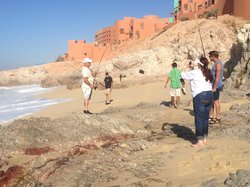 People fishing on the beach below the complex