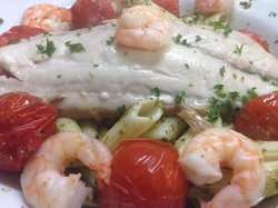red snapper on a bed of pesto pasta with prawns and cherry tomatoes