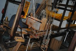 Professional artist working on wooden loom in the Brocade Museum