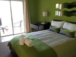 """Cozy queen bed in the """"Coco Plum"""" suite."""