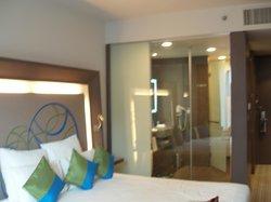 Partisi kaca antara kamar tidur dan kamar mandi. Era design hotel masa kini