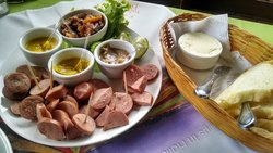 Prato com salsichão, molhos diferenciados e acepipes