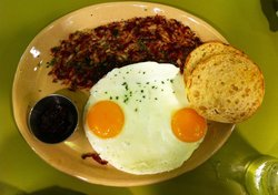Corned beef hash with eggs over easy and English muffin