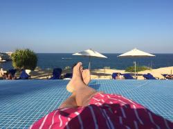les doigts de pieds en éventail sur la terrasse innondée de la piscine.