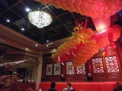 Kopf des Drachens aus Luftballons wie er sich an der Decke entlang schlängelt
