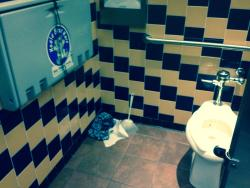Dirty underwear in the corner near the baby changing area in the men 's restroom on 4/10/15.