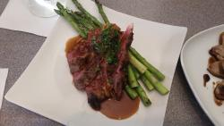 Flat iron steak cooked rare with a glaze and perfectly cooked asparagus